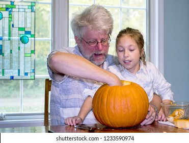 A little girl watches as her grand dad scoops out the inside of a pumpkin for a halloween jack o lantern