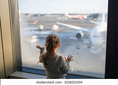 Little girl watching an airplane at the airport
