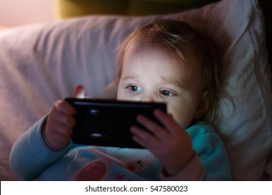Little girl watching cartoon on mobile device.