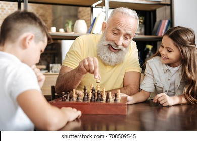 Little girl watching her brother and grandfather play chess