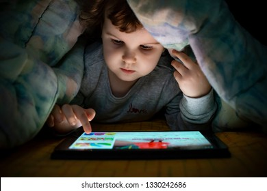 Little girl watching her tablet in the bed. Illuminated child face from device screen. Child dressed with pajamas under the covers hold a tablet. Night time.