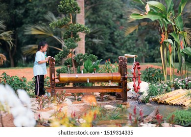 Little girl is watching the musical water wheel, inventive traditional system to irrigate water while making a beautiful sound.