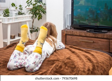 Little girl watching television on the sofa at home