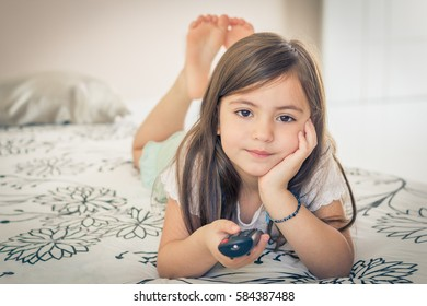 Little girl watching TV lying on bed with remote control in hand