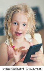 little girl watching video or playing game on smartphone