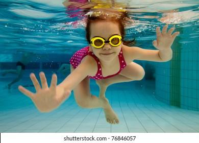 La petite fille dans le parc aquatique nageant sous l'eau et souriante