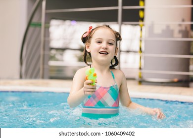 Little girl with a water pistol in a swimming pool. Childhood games. Water park.