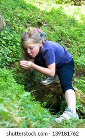 Little girl at the water source in the forest