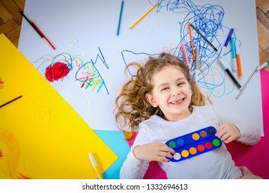 Little girl with watercolor set and crayons. Happy kids learning concept.
