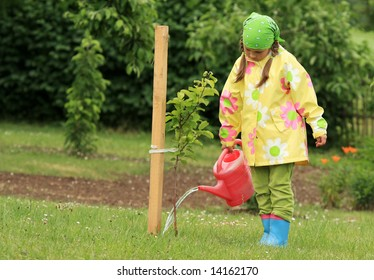 Little girl watering apple tree with watering pot