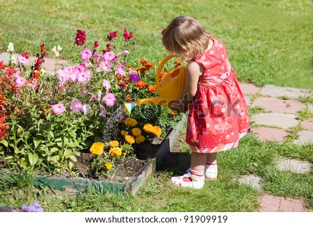 Little girl watering flower beds