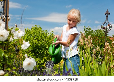 Little girl watering the flowers in the family garden at a summer day, very rural scene