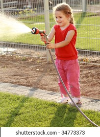 Little girl watering the grass in the garden