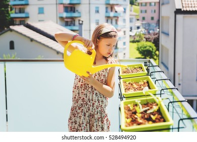 Little girl watering plants on the balcony