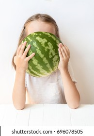 A little girl is a watermelon, croaks, laughs, humor, emotions, eat watermelon