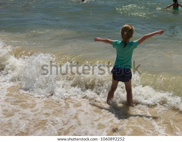 Little girl in a wave of a sea called her friend.