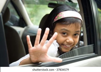 Little girl waving goodbye from inside of a car