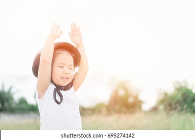 Little girl wear helmet and praying and raise hands in the morning for faith, spirituality and religion.Trust ind GOD concept.