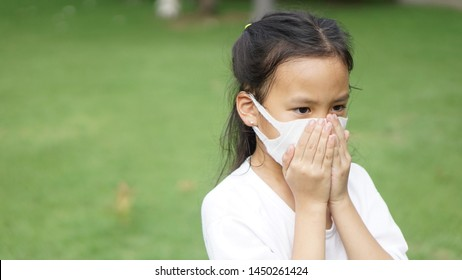little girl wear protect mask and close her mouth on green grass