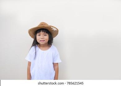 A little girl is wearing a basketry hat.