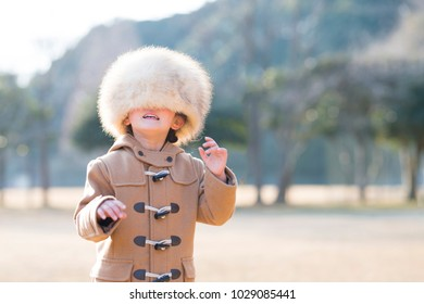 Little girl wearing too big a fur hat