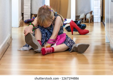 Little girl wearing big high-heeled mother's shoes.