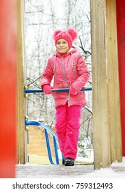 Little girl wearing bright pink clothes on the playground outdoors in winter park