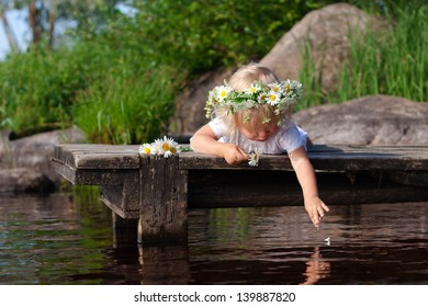 Little girl wearing chamomile wreath is dropping petal into the water