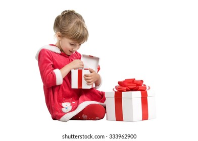 little girl wearing a Christmas costumes. she sits on a white background and opens a cardboard box with a gift. isolated