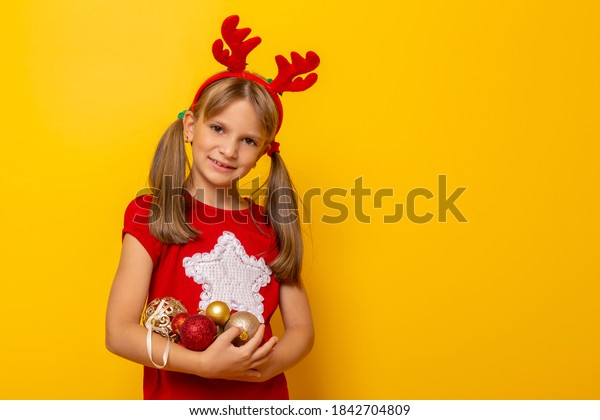 Little girl wearing costume reindeer antlers holding a handful of Christmas tree decorations and smiling isolated on yellow colored background