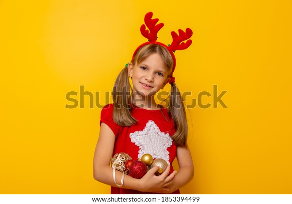 Little girl wearing costume reindeer antlers holding a handful of Christmas tree ornments and smiling isolated on yellow colored background
