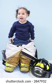 Little girl wearing daddy's big fireman pants and boots