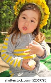 little girl wearing dandelion diadem eating a slice of apple (talking)