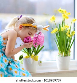 Little girl wearing Easter bunny ears decorating home for holidays. Happy child enjoying beautiful blooming early spring flowers on the window.