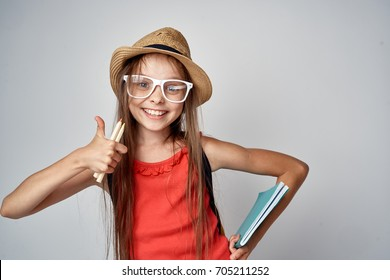 little girl wearing glasses and wearing a hat on gray background smiling.