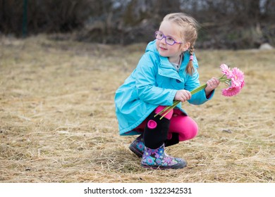 a little girl wearing glasses sitting in grass and holding a violet flower