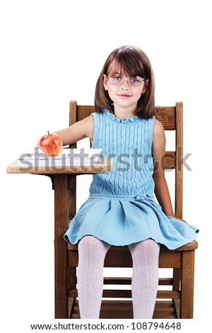 17aa2f63a7 Little girl wearing glasses sitting at a school desk with apple and books.  Isolated on a white background with clipping path included. - Image