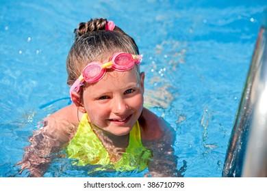 Little girl wearing goggles in swimming pool.