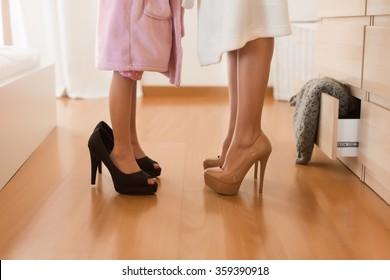 Little girl wearing heels with her mother in bedroom