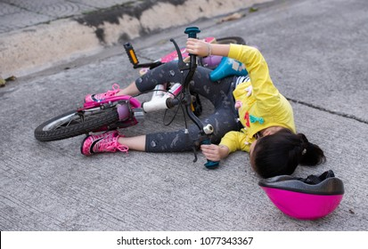 The little girl wearing a helmet bicycle riders collided with a car, until the fall has been injured in the middle of the road