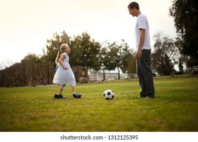 Little girl wearing her father's shoes has fun playing soccer with him on the lawn.