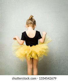 Little girl wearing leotard and tulle tutu viewed from behind