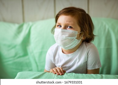 a little girl, wearing a medical mask, plays at home, in home quarantine, during the coronavirus pandemic,COVID-2019
