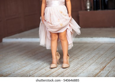 A little girl wearing mums shoes and beautiful dress