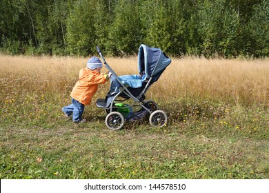 Little girl wearing orange jacket rolls blue baby carriage; green field and forest