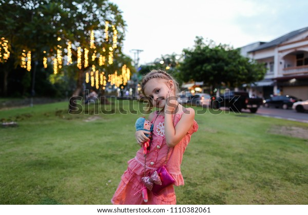 Little girl wearing pink dress with toy standing on lawn in city. Concept of summer vacations and childhood.