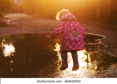 little girl, wearing a pink jacket,  jumps into a puddle