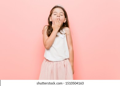 Little girl wearing a princess look yawning showing a tired gesture covering mouth with hand.