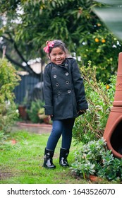 A little girl wearing a rain coat with rain boots that is standing outside in a mexican style garden, while its raining.