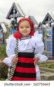 Little girl wearing romanian traditional clothing and traditional cemetery of Sapanta on a background